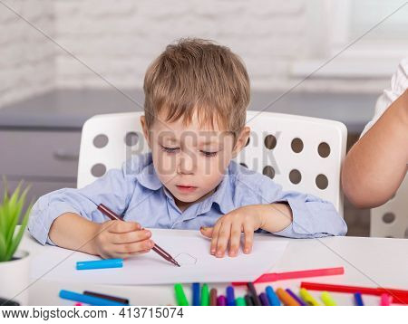 Beautiful Boy Drawing Picture With Pencil In Art Class. Cute Cheerful Child Drawing Using Felt-tip P
