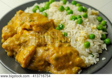 Chicken Breast Pieces In A Mildly Spiced Coconut Curry Sauce With Fried Rice With Peas And Egg, Indi