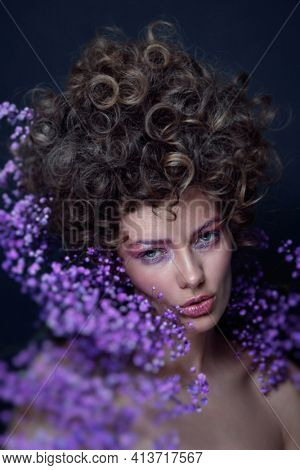 Vintage style portrait of beautiful young woman with fancy hairdo and violet flowers around her face, soft focus, grainy
