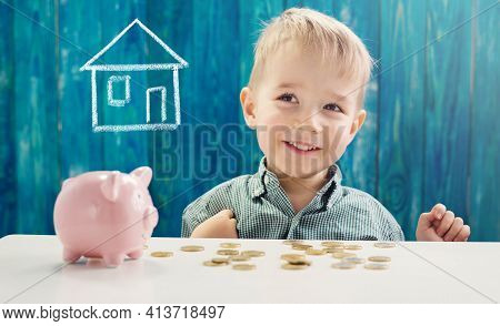 Three Years Old Child Sitting St The Table With Money And A Piggybank. Happy Boy With Euro Coins. Ki