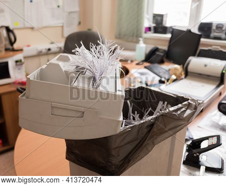 Open Cover Of Paper Shredder With Scraps Of Paper On The Table In The Office. Close-up.