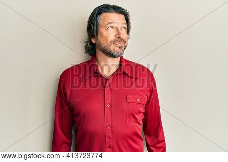 Middle age handsome man wearing casual clothes smiling looking to the side and staring away thinking.