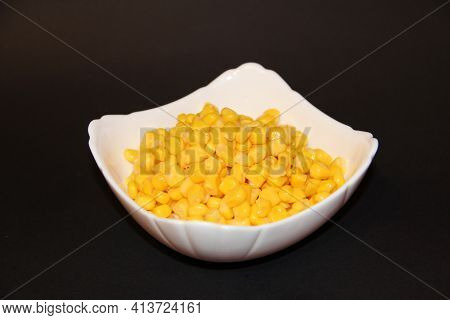 Canned Sweet Corn In White Ceramic Bowl Isolated On Black. Heap Of Corn Kernels In Plate Close Up. F