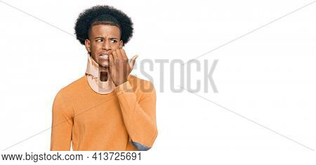 African american man with afro hair wearing cervical neck collar looking stressed and nervous with hands on mouth biting nails. anxiety problem.
