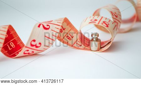 Measuring Tape With A Small Weight Of Weights On A White Background. A Photo Showing Slow Weight Los