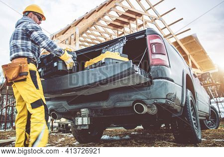 Caucasian Construction Contractor Worker In His 40s Taking Tools Boxes From Bed Section Of His Picku