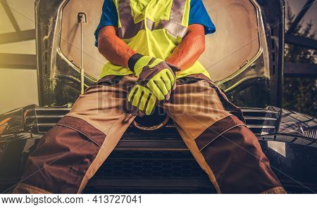 Hopeless Car Mechanic Seating On The Car Engine Compartment With No Hope For Successful Fix. Automot