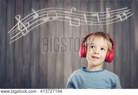 Happy Little Boy On Wooden Background With Red Headphones. Child Listening Music With Wireless Heads