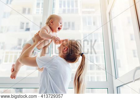 Mother Playing With Newborn Baby Son At Home. Woman Tossing Kid Up On Balcony. Happy Infant Wearing