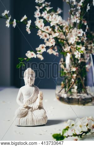 Decorative White Buddha Statuette With Blooing Tree Branches In The Vase On The Dark Background. Med