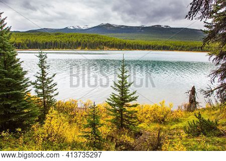 Lake Maligne in the snow-capped mountains is surrounded by coniferous evergreen forests. Cold cloudy fall day in the Canadian Rockies