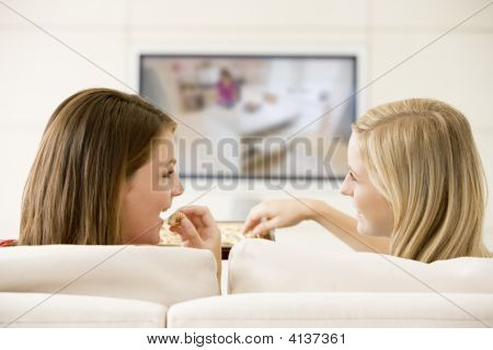 Two Women In Living Room Watching Television Eating Chocolates Smiling
