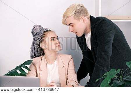 Young Colleagues Man And Woman Flirting At Work. Woman Sitting At Desk In Office Looks Into The Eyes