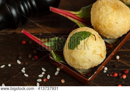 Arancini, A Traditional Italian Appetizer, Fried Rice Balls With Mozzarella. Close-up On A Dark Wood