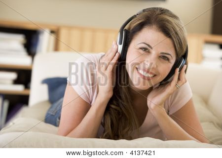 Woman In Living Room Listening To Headphones Smiling