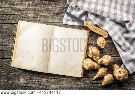 Blank cookbook and raw jerusalem artichoke. Topinambur vegetable root on wooden table. Top view.