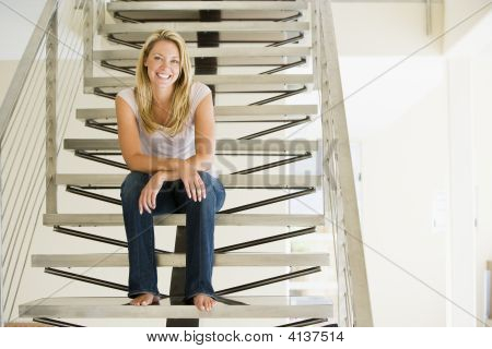 Woman Sitting On Stairs Smiling