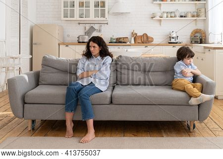 Annoyed Mom And Stubborn Child Sitting On Couch At Home, Ignoring Each Other, Posture Of Discontent.