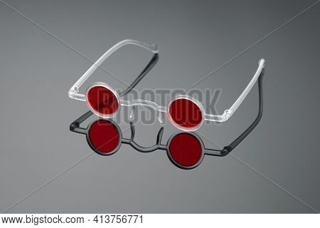 Extravagant Glasses With Red Round Glasses In White Frame On Mirror-gray Background. Creative And Fa