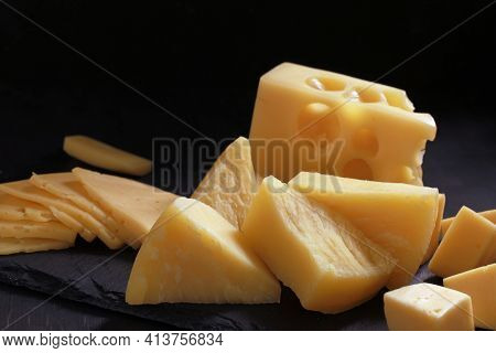 Assortment Of Different Types Of Cheese On Dark Background. Cheese Background.