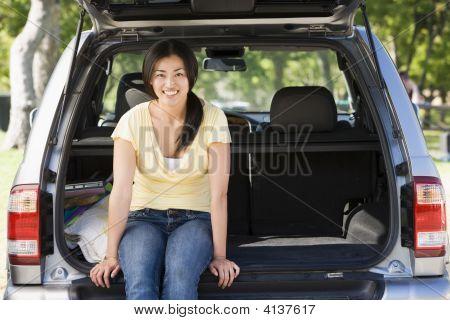 Woman Sitting In Back Of Van Smiling