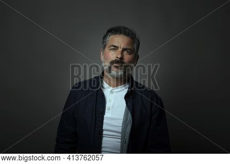 Portrait Of A Forty Year Old Caucasian Man Wearing A Denim Shirt Overlay. Black Background, Dark Con