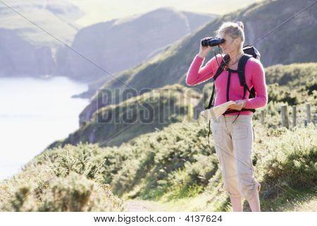 Woman On Cliffside Path Using Binoculars