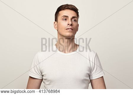 Pensive handsome man stands on white background. Athletic man posing at studio. Men's health.