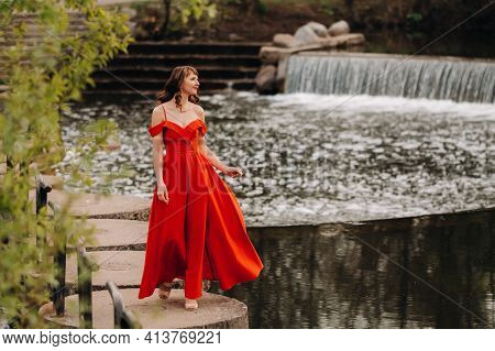 Girl In A Long Red Dress Near The Lake In The Park At Sunset.