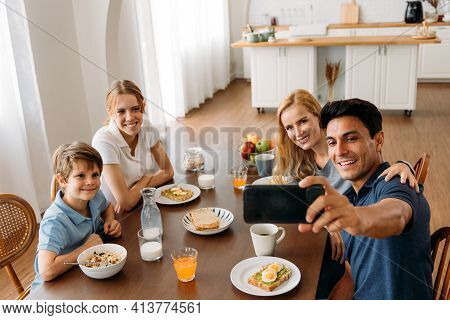Caucasian Family Group Of Four Taking Selfie Photo While Eating A Breakfast On Dining Table. Father,