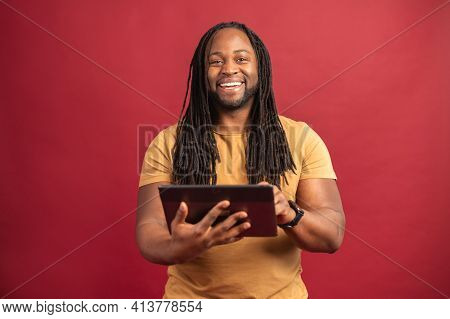 Happy Smiling African American Man With Dreadlocks Standing Isolated Over Red Background, Pressing P