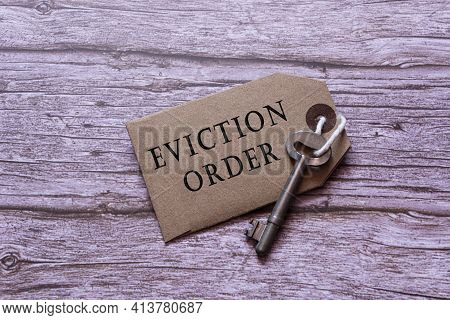 Text On Brown Tag With House Key On Wooden Table - Eviction Order