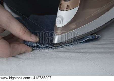 The Process Of Ironing The Legs Of Jeans With An Iron. Iron Spout And Hand Close-up. Care Of Fabrics