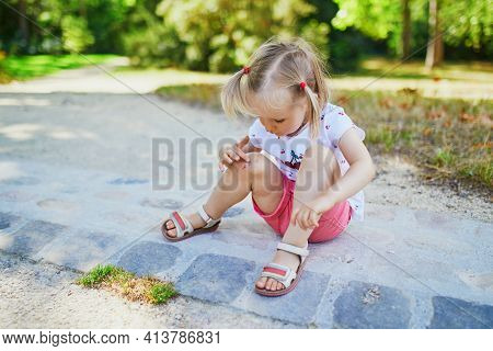 Cute Little Toddler Girl Sitting On The Ground After Falling At Summer Park. Child Getting Hurt Whil