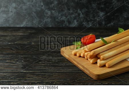 Board With Grissini Breadsticks On Wooden Table