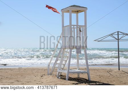 Empty Lifeguard Tower And Red Storm Flag On The Beach In Stormy Weather. Lack Of Lifeguards On The B