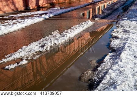 Spring Slush And Large Puddles On A City Street With A Reflection Of A Brick Building. Asphalt Road