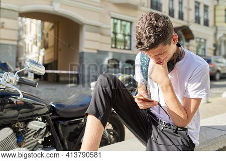 Boy Teenager 16, 17 Years Old, Using Smartphone, Sitting On Street Of Summer City