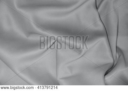Abstract Background Of Luxurious Fabric, Folds In The Waves Of Silk Fabric. The Texture Of The Satin