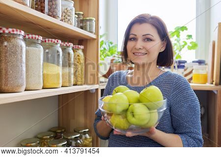 Woman With Bowl Of Green Apples In Pantry, Organizing In Kitchen