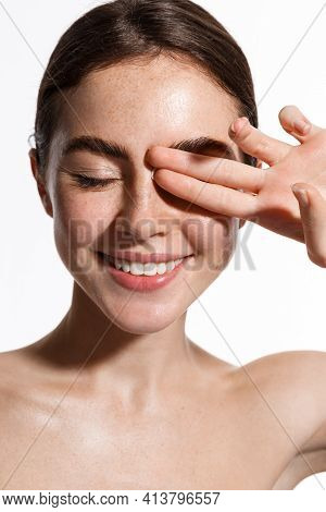 Vertical Shot Of Beauty Woman Naked, Touching Fresh And Clean, Hydrated Facial Skin, Close Eyes And
