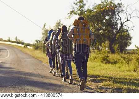 Group Of Young Hikers Walk In A Row Along The Road With Backpacks On Their Shoulders.