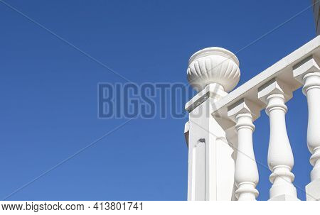 Sun-drenched White Balustrade On Blue Sky Background. Pillar Finished With Decorative Planter Made O