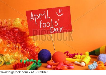 Sign With Phrase Happy Fools' Day And Clown's Accessories On Orange Background