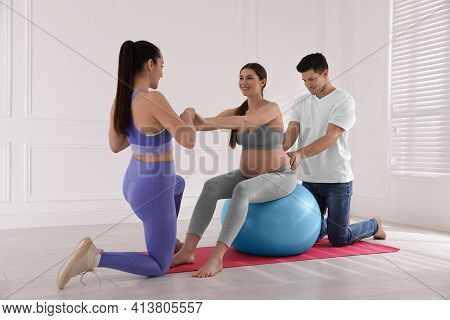 Pregnant Woman And Her Husband Working With Trainer In Gym. Preparation For Child Birth