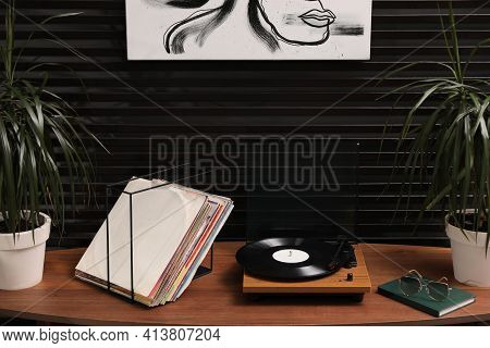 Stylish Turntable With Vinyl Discs On Table In Room