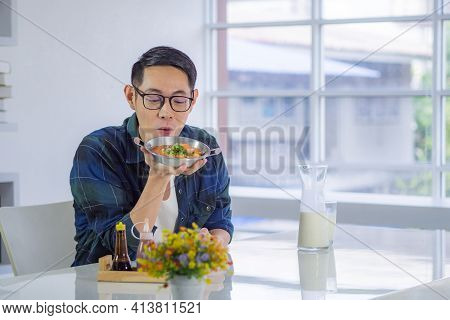 Young Man Wearing Glasses Sitting Looking At The Fried Egg Served On A Pan With Colorful Toppings Se