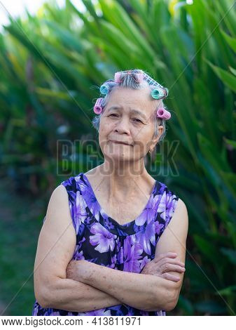 Portrait Of Senior Woman Hair Curlers,  Arms Crossed And Looking At The Camera While Standing In A G