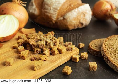 Scattered Croutons With Onions On A Wooden Board In A Close-up, Still Life, Homemade Croutons