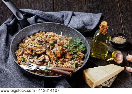Classic Creamy Mushroom Risotto Sprinkled With Grated Parmesan Cheese In A Pan And Ingredients On A